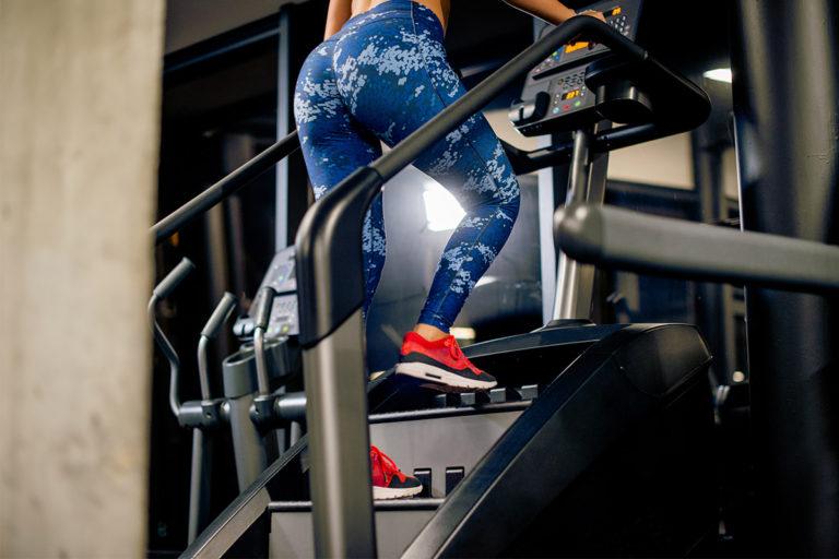 Fata care face exercitii pe stair stepper.