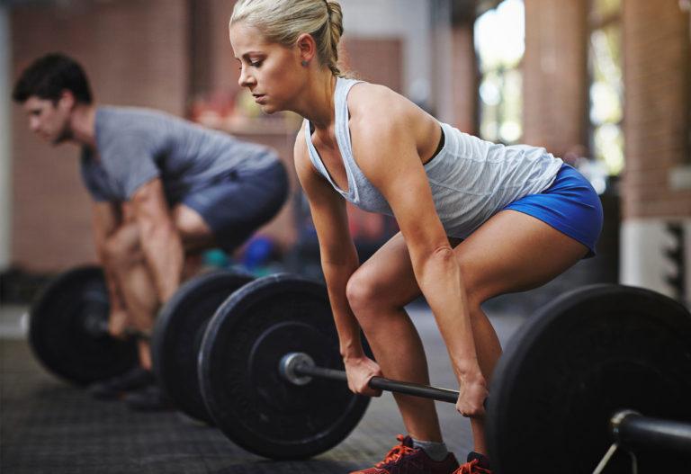 Femeie si barbat care se antreneaza cu greutati.