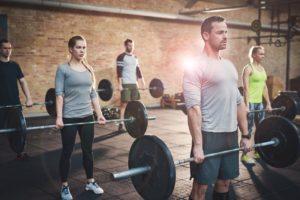 Mai multe persoane care se antreneaza ridicand greutati.