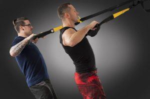 Doi barbati care se antreneaza cu echipament TRX.