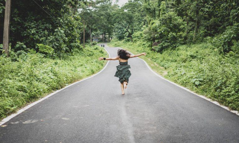 Fata care alearga pe un drum asfaltat