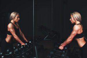 Femeie apucând greutăți în timp ce se privește în oglindă