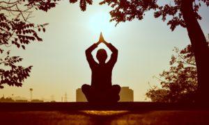 Silueta unei fete care face yoga.