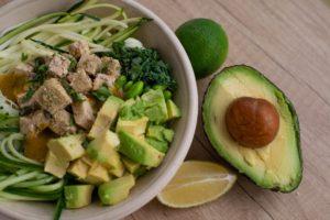 Un avocado copt lângă un bol de salată