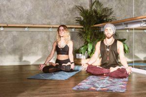 Barbat si femeie care fac yoga.