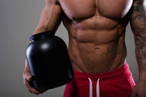 Atlet ce ține în mână un supliment pe bază de creatină