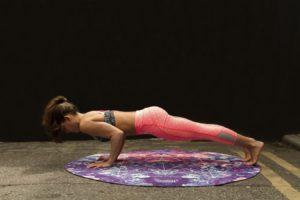 Femeie făcând exerciții la saltea pentru a-și tonifia musculatura