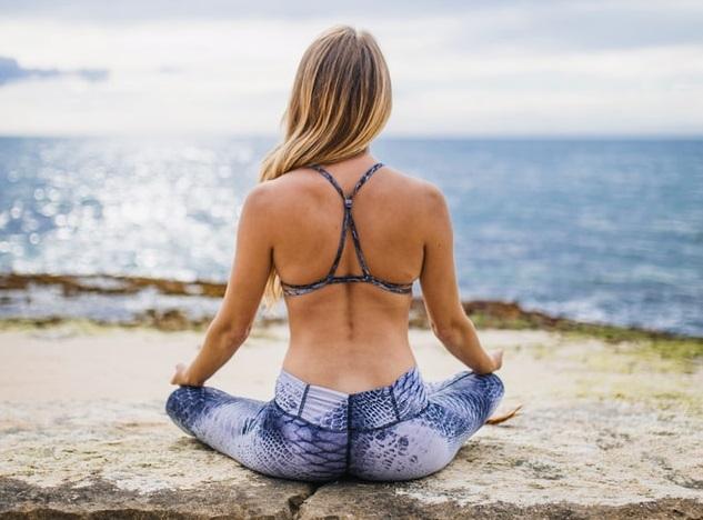 Femeie cu un spate lucrat stând într-o poziție de yoga