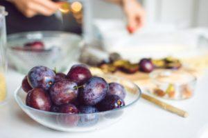 Bol de prune pe o masă
