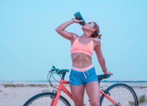 Femeie pe bicicletă luând o pauză pentru hidratare