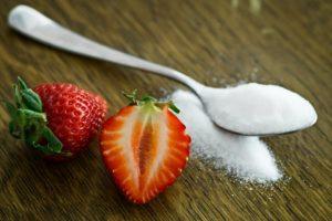 Lingură cu zahăr alături de două căpșuni