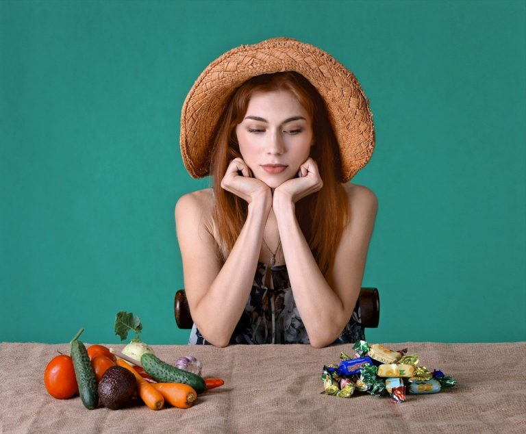 Tânără indecisă în a alege alimente sănătoase sau dulciuri