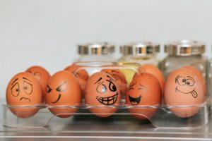 Ouă desenate cu diferite chipuri sunt ținute în frigider