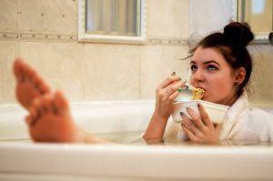 Tânără mănâncă compulsiv în timp ce face baie