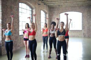 Femei susțin un antrenament de aerobic cu greutăți într-o sală de forță