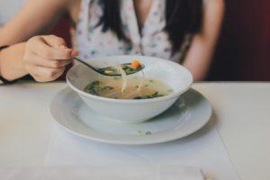 Femeie servește o supă de pui cu tăiței