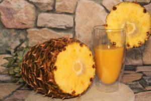 Pahar cu suc de ananas alături de un ananas întreg