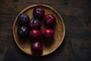 Prune proaspete puse într-un bol de lemn