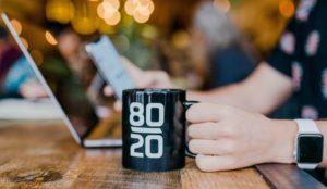 Tânăr se documentează pe laptop despre regula 80/20