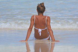 Tânără își expune corpul la soare pe malul mării