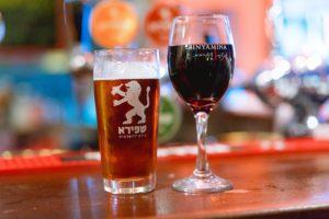 Un pahar de vin si un pahar de bere expuse pe un bar