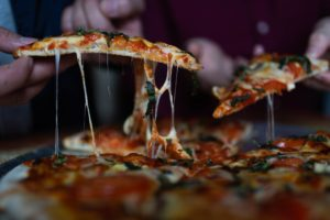 Persoane servesc felii de pizza