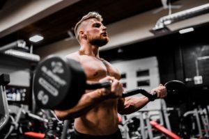 Tânăr sportiv își lucrează bicepsul cu bara în z