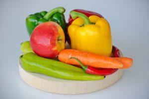 Fructe și legume așezate pe un tocător de lemn