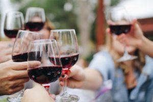 Grup de prieteni ciocnesc un pahar de vin roșu