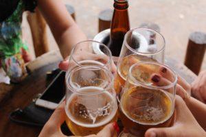 Persoane ciocnesc pahare cu bere