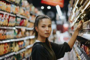 Tânără alege produse de pe raionul unui supermarket