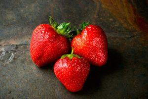 Trei căpșuni proaspăt culese, de dimensiuni diferite