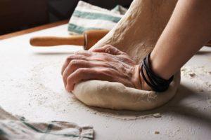 Femeie frământă aluat pentru pâine