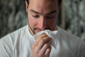 Tânăr își suflă nasul din cauza răcelii