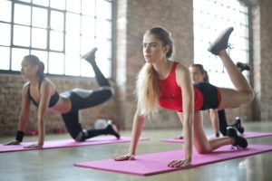 Tinere lucrează exerciții de tip yoga