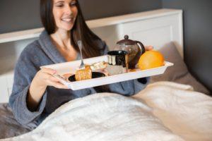 Tânără servește micul dejun în pat