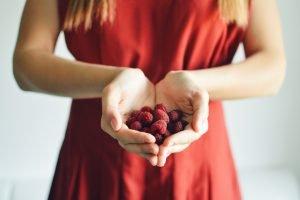 Tânără în rochie roșie ține în pumn zmeură