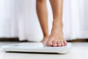 Femeie pășește pe cântar pentru a-și afla greutatea corporală