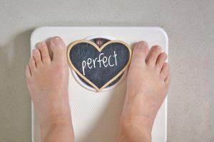 Tânără se cântărește dorind să piardă constant în greutate