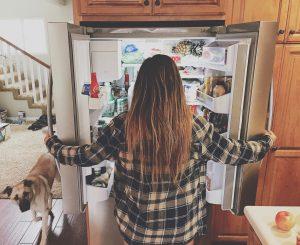 Tânără deschide larg frigiderul