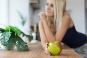 Tânără suplă ține în mână un măr proaspăt cules