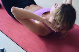 Tânără susține exerciții pentru mușchii abdominali
