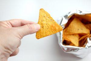 Bărbat mănâncă un chips din porumb direct din pungă