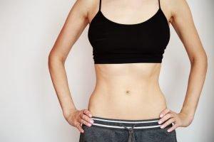 Femeie tânără abdominală își expune zona abdominală