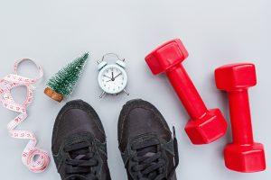 Pantofi sport, gantere și un ceas ce semnifică trecerea dintre ani