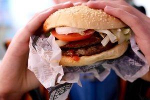Tânăr mușcă dintr-un hamburger