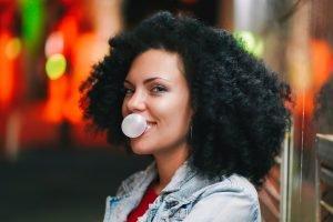 Tânără face un balon din gumă de mestecat