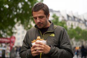 Tânăr mănâncă un hamburger pe stradă