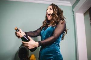 Tânără deschide o sticlă de șampanie