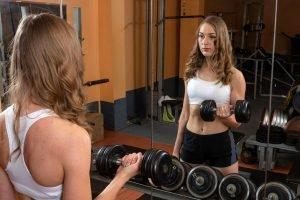 Tânără se antrenează cu gantere în sala de fitness